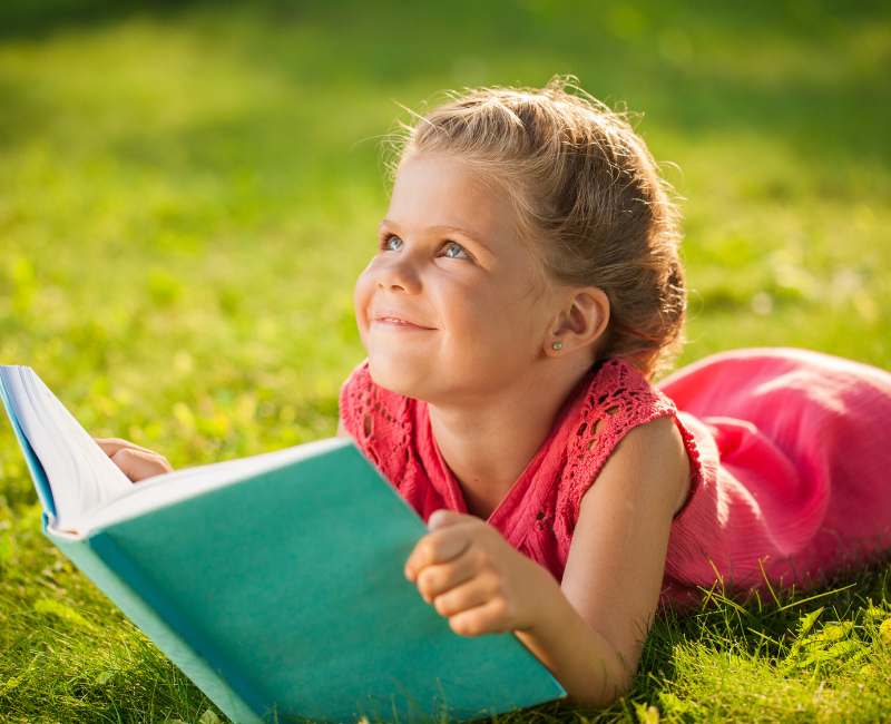 Literacy practice. Girl on lawn reading book