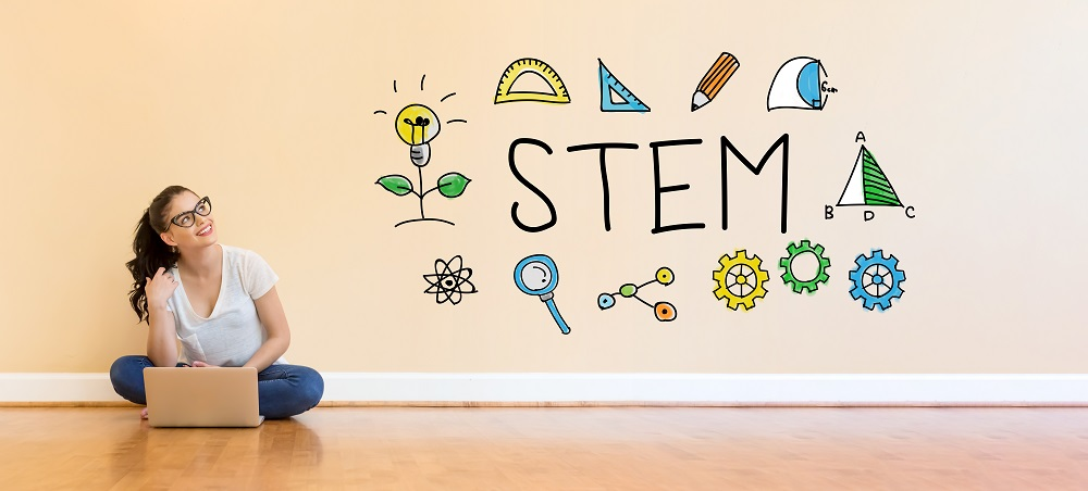 Best STEM Careers for women. woman sitting on floor looking at STEM written in the air.