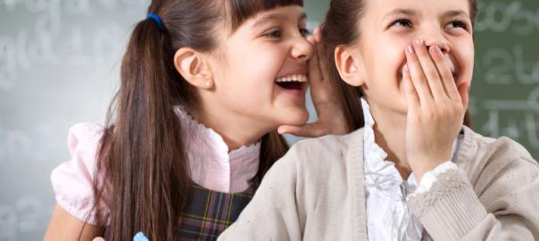 Education feed. Girls doing school work whispering in other's ear.