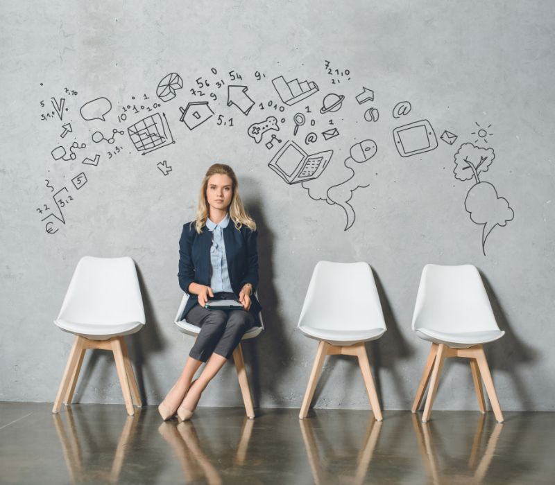 Interview Skills Guide. Young woman sitting in a waiting room chair with symbols on the wall behind her.