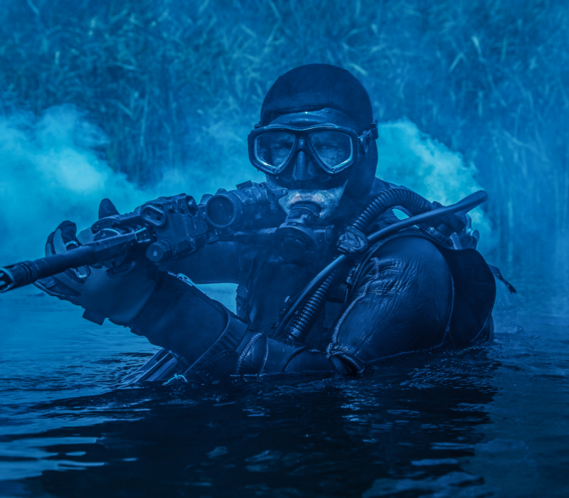 Navy army practice. Marine in water with a gun.