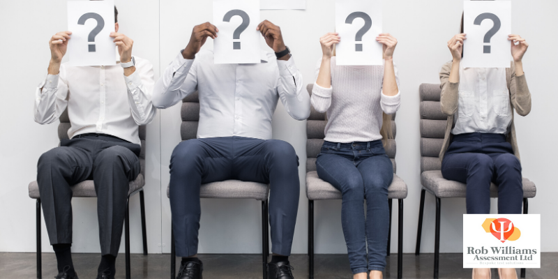 Interview Skills Guide. Interview candidates sitting in a row with question mark in front of their faces.