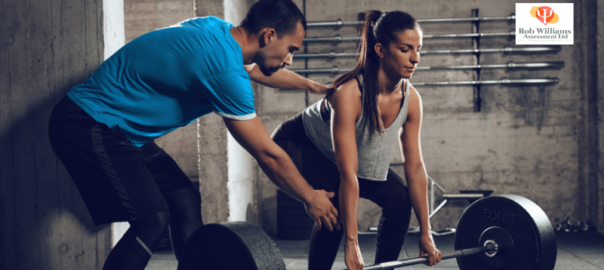 Joga Training Jobs - Personal trainer helping woman with weights