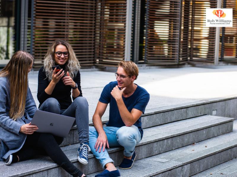 University students sitting on steps sharing university application tips.